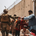 FILE PHOTO: A U.S. Marine passes out water to evacuees during an evacuation at Hamid Karzai International Airport, Kabul, Afghanistan, August 22, 2021. Picture taken August 22, 2021.  U.S. Marine Corps/Sgt. Isaiah Campbell/Handout via REUTERS THIS IMAGE HAS BEEN SUPPLIED BY A THIRD PARTY./File Photo